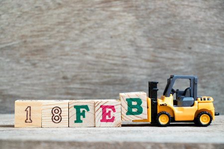 Toy forklift hold block B to complete word 18feb on wood background (Concept for calendar date 18 in month February) Stock Photo