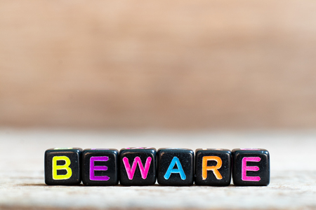 Black bead with color alphabet in word beware on wood background