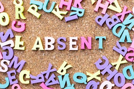 Alfabeto de color en la palabra ausente con otra letra como marco sobre fondo de tablero de corcho Foto de archivo