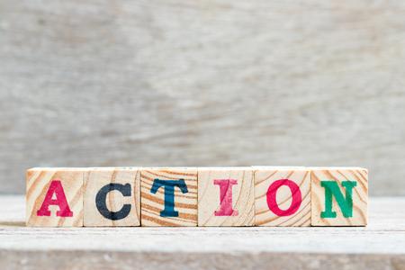 Buchstabenblock in Wortaktion auf Holzhintergrund