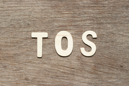 Alphabet letter in word TOS (abbreviation of Terms of service) on wood background 스톡 콘텐츠