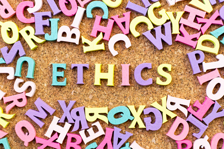 Color alphabet in word ethics with another letter as frame on cork board background Banco de Imagens