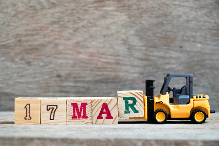 Toy forklift hold block R to complete word 17mar on wood background (Concept for calendar date 17 in month March)