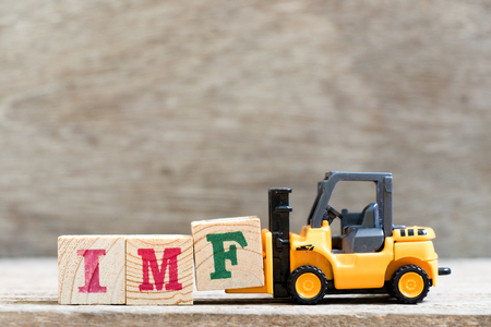 Toy forklift hold letter block f in word IMF (Abbreviation of International Monetary Fund) on wood background Banco de Imagens