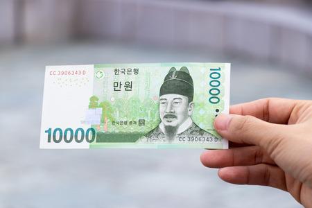 Man hold south korea banknote 10000 won on blurred background Stockfoto