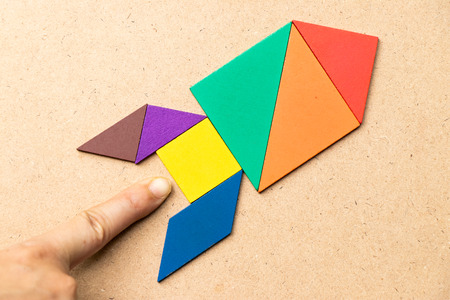 Color tangram in rocket shape with hand at the base on wood background (Concept for startup, new experience or business) Stock fotó