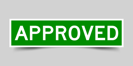 Green and white sticker with word approved on gray background