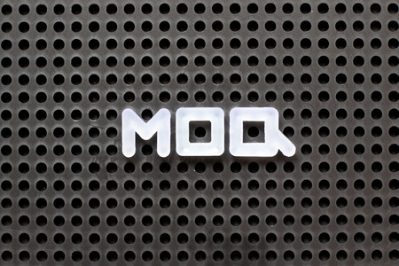 Black color pegboard with white letter in word MOQ (Abbreviation of Minimum Order Quantity)