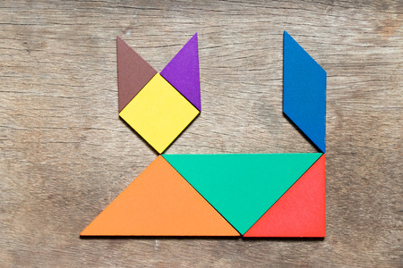 Color tangram in lying cat shape on wood background