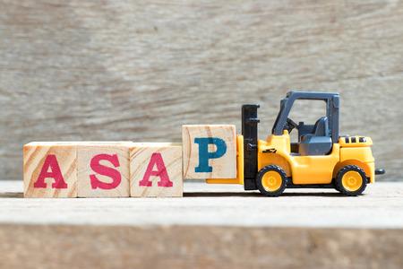 Toy carrello attesa lettera blocco p per completare la parola al più presto (abbreviazione di appena possibile) su uno sfondo di legno Archivio Fotografico