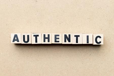 Bloc de lettre de l'alphabet dans le mot authentique sur fond de bois