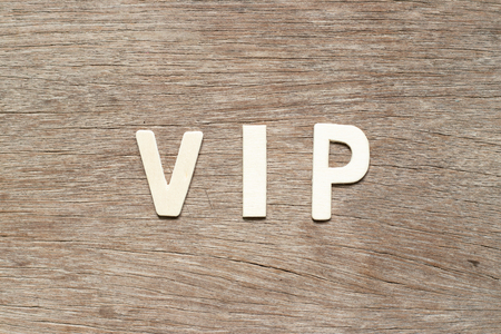 Alphabet letter in word VIP (abbreviation of very important person) on wood background 免版税图像