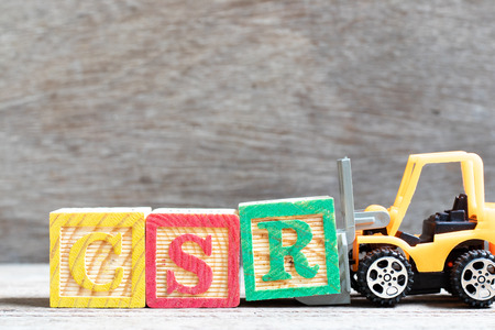 Toy forklift hold letter block R in word CSR (Abbreviation from corporate social responsibility) on wood background