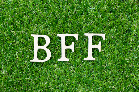 Wood letter block in word BFF (Abbreviation of best friend forever) on artificial green grass background