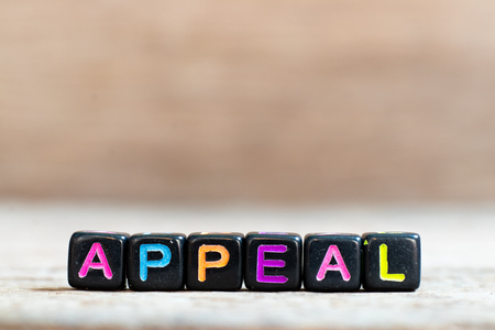 Black bead with color alphabet in word appeal on wood background Stock Photo