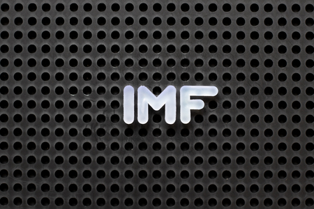 Black color pegboard with white letter in word IMF (abbreviation International Monetary Fund)