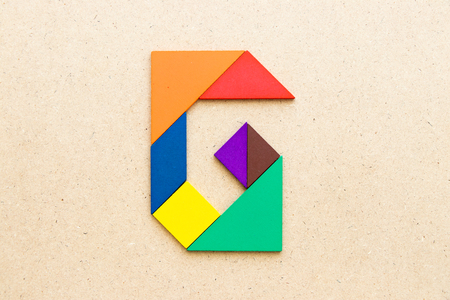 Tangram puzzle in alphabet letter G shape on wood background 스톡 콘텐츠