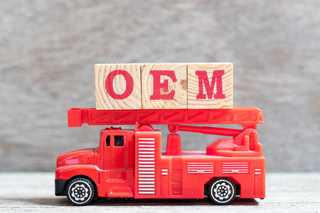 Red fire truck hold letter block in word OEM (Abbreviation of Original Equipment Manufacturer) on wood background