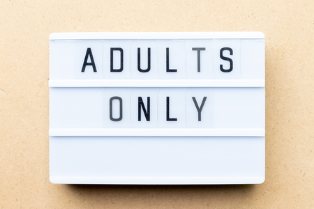 White lightbox with word adults only on wood background