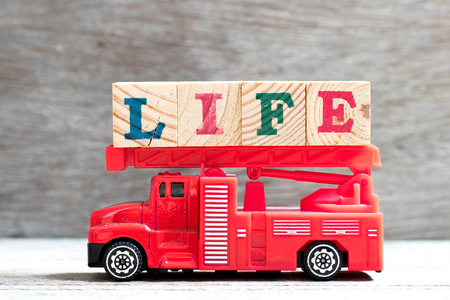 Toy fire ladder truck hold letter block in word life on wood background Фото со стока