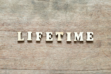 Letter block in word life time on wood background