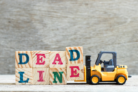 Toy forklift hold letter block d, e to complete word deadline on wood background Banque d'images - 118513883