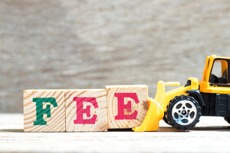 Toy bulldozer hold letter block e to complete word fee on wood background Stock Photo