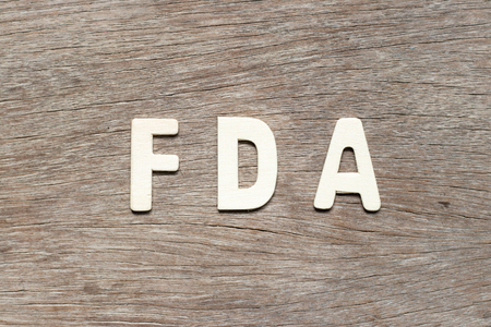 Alphabet letter in word FDA (abbreviation of food and drug administration) on wood background Stock Photo
