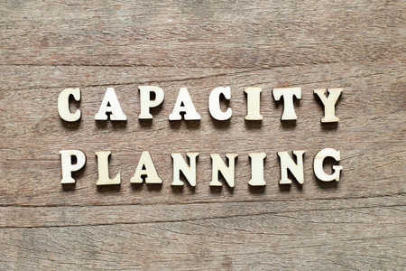 Letter block in word capacity planning on wood background