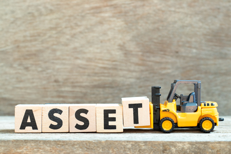 Toy forklift hold letter block t to complete word asset on wood background Stock Photo