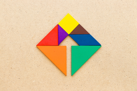 Color tangram puzzle square with arrow inside shape on wood background