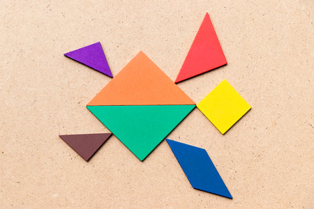 Color tangram in swimming turtle shape on wood background