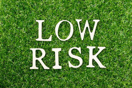 Wood alphabet letter in word low risk on green grass background