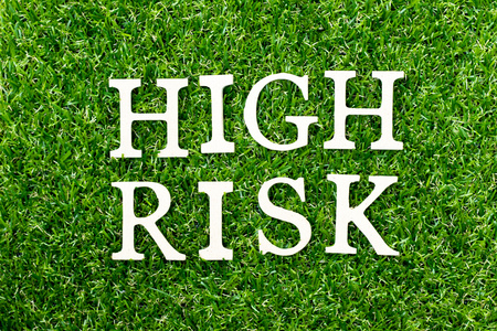 Wood alphabet letter in word high risk on green grass background Stock Photo
