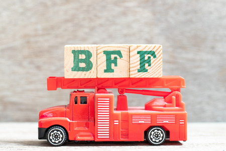 Red fire truck hold letter block in word BFF (Abbreviation of best friend forever) on wood background
