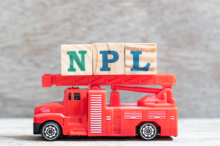 Red fire truck hold letter block in word NPL (Abbbreviation of Non Performing Loan, Non-Patent Literature)  on wood background