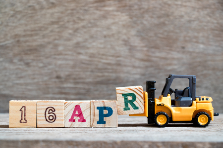 Toy forklift hold block R to complete word 16apr on wood background (Concept for calendar date 16 in month april) Stock Photo