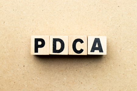 Alphabet letter block in word PDCA (business abbreviation of plan do check act) on wood background