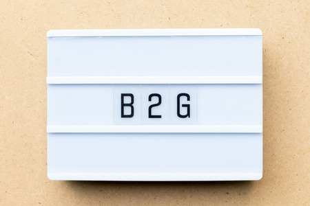 White lightbox with word b2g (abbreviation of business to government) on wood background 写真素材