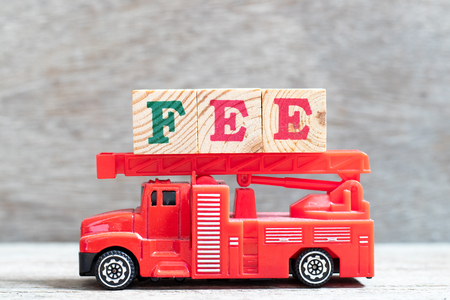 Red fire truck hold letter block in word fee on wood background