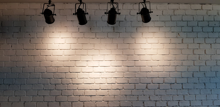 Hanging spotlight illuminate at white brick wall background with copy space 免版税图像