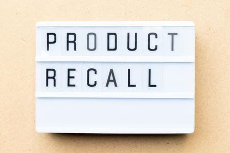 White lightbox with word product recall on wood background