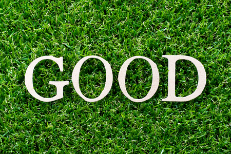 Wood letter in word good on artificial green grass background
