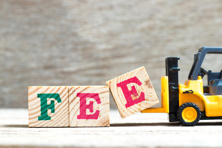 Toy forklift hold letter block e to complete word fee on wood background Stock Photo
