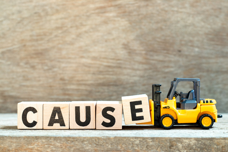 Toy forklift hold letter block e to complete word cause on wood background Stok Fotoğraf