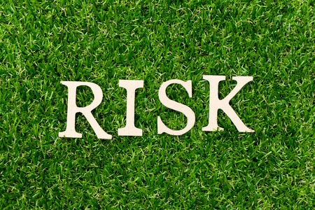 Wood letter in word risk on green grass background