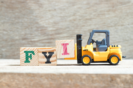 Toy forklift hold letter block I to complete word FYI (Abbreviation of For your information) on wood background
