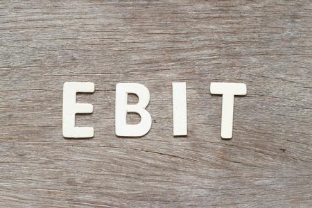 Letra del alfabeto en la palabra EBIT (abreviatura de ganancias antes de intereses e impuestos) sobre fondo de madera Foto de archivo