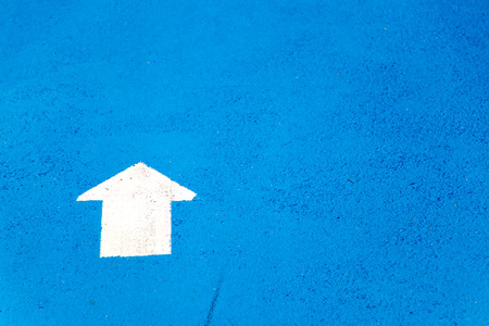 White painting in forward direction arrow symbol on blue concrete road background 스톡 콘텐츠