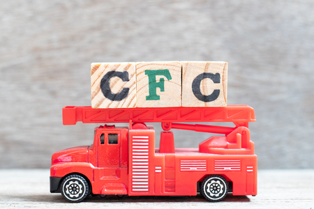 Red fire truck hold letter block in word CFC (abbreviation of Chlorofluorocarbon) on wood background Фото со стока